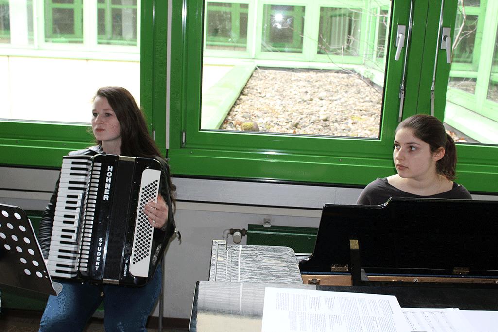 Schülerin am Akkordeon und andere Schülerin am Klavier